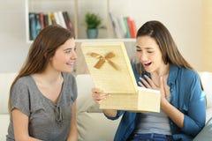 Deux amis ouvrant un boîte-cadeau à la maison Images libres de droits