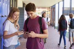 Deux amis parlant et à l'aide des téléphones dans le couloir d'école Images libres de droits