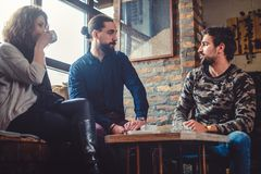 Deux amis parlant tandis que l'amie boit du café Photographie stock libre de droits