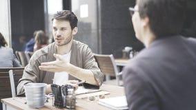 Deux amis parlent à la table du café dehors Photos libres de droits