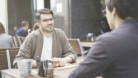 Deux amis parlent à la table du café dehors Photo libre de droits