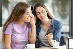 Deux amis partageant sur la ligne musique dans une barre Image stock