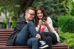 Deux amis partageant un smartphone sur un banc de parc Photos stock