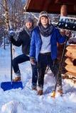 Deux amis pellant la neige de la cour en cottage d'hiver Image stock