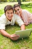 Deux amis pensant à l'avenir comme ils utilisent une tablette ensemble Photo libre de droits