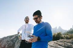 Deux amis pilotent le bourdon sur la montagne Image libre de droits