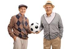 Deux amis pluss âgé tenant un football Photographie stock