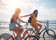 Deux amis pour un tour de vélo sur la promenade de bord de la mer Images libres de droits