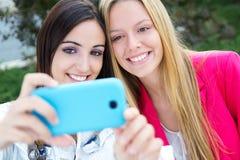 Deux amis prenant des photos avec un smartphone Images libres de droits