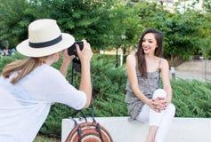 Deux amis prenant des photos en parc Images libres de droits