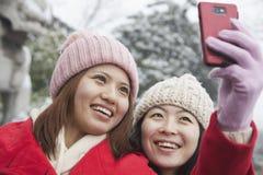 Deux amis prenant la photo avec le téléphone portable dans la neige Photos stock