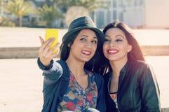 Deux amis prenant le selfie avec un filtre ont appliqué le style d'instagram Photographie stock