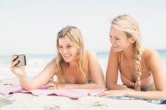 Deux amis prenant le selfie tout en se trouvant sur la plage Photographie stock libre de droits