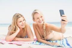 Deux amis prenant le selfie tout en se trouvant sur la plage Images stock