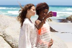 Deux amis prenant un selfie à la plage Images stock