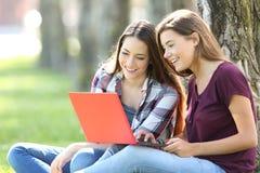 Deux amis recherchant le media en ligne dans un ordinateur portable Photographie stock libre de droits