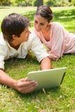 Deux amis regardant l'un l'autre tout en à l'aide d'une tablette ensemble Photographie stock libre de droits
