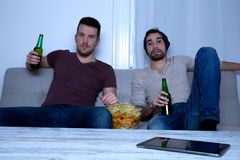 Deux amis regardant la télévision à la maison Images stock