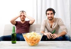 Deux amis regardant la télévision à la maison Images libres de droits