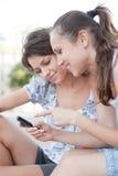 Deux amis regardant le portable Images stock