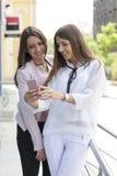 Deux amis regardant un téléphone portable, ils sont heureux et smilin Photos stock