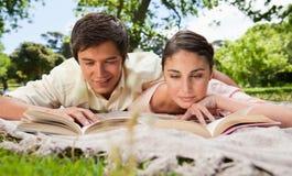 Deux amis regardant vers le bas des livres tout en se trouvant sur une couverture Photo stock