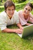 Deux amis regardant vers le côté tout en à l'aide d'un ordinateur portable Image libre de droits