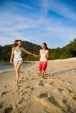 Deux amis retenant des mains fonctionnant le long de la plage Image stock