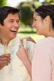 Deux amis riant tout en retenant des glaces de champagne Photo stock