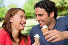Deux amis riant tout en retenant la crême glacée Photographie stock