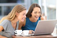 Deux amis riant wathing sur la ligne contenu Images stock