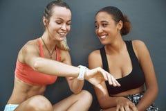 Deux amis riants vérifiant leur temps après une course ensemble photo stock