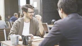 Deux amis rient de la table du café dehors Photographie stock