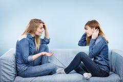 Deux amis sérieux de femmes parlant sur le sofa Images libres de droits