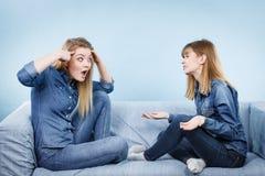 Deux amis sérieux de femmes parlant sur le sofa Photographie stock libre de droits