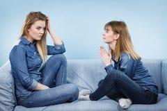 Deux amis sérieux de femmes parlant sur le sofa Image libre de droits