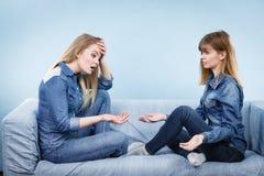 Deux amis sérieux de femmes parlant sur le sofa Photographie stock