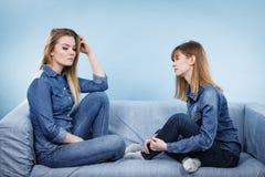 Deux amis sérieux de femmes parlant sur le sofa Photo libre de droits