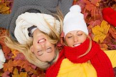 Deux amis s'étendant dans des feuilles avec les yeux fermés Photo stock