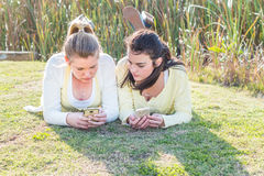 Deux amis s'étendant sur l'herbe en parc agissant l'un sur l'autre Photographie stock