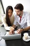 Deux amis s'asseyant à la table avec l'ordinateur portable Images stock