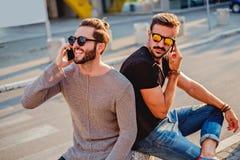 Deux amis s'asseyant dans la rue, parlant au téléphone Images stock