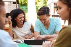 Deux amis s'asseyant dehors par la table Image libre de droits