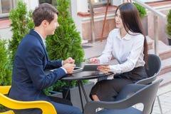 Deux amis s'asseyant en café et discutant leurs affaires Photographie stock libre de droits