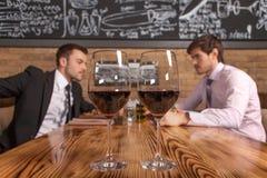 Deux amis s'asseyant en café et mangeant le déjeuner Photographie stock