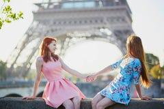 Deux amis s'asseyant près de Tour Eiffel à Paris, France Photographie stock