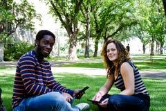 Deux amis s'asseyant sur l'herbe Image stock