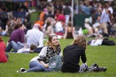 Deux amis s'asseyant sur l'herbe en parc Photographie stock