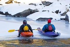 Deux amis s'asseyant sur la glace dans des kayaks colorés Photos stock