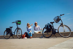 Deux amis s'asseyant sur la plage avec des bicyclettes Photographie stock